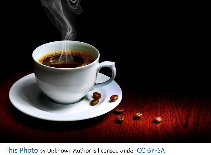 A steaming cup of black coffee is in a white mug on a white plate with coffee beans on the white plate and wood table.