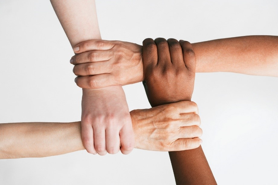 Four persons are using their right hands to make a square knot  by each hand holding the other persons wrist. The viewer sees the human knot from above. The ethnicity of the different hands implies persons of African, Asian, Hispanic, and Caucasian descent ,